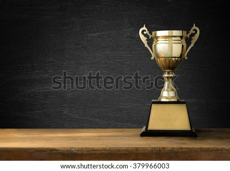 Trophies placed on a wooden table with blackboard background  #379966003