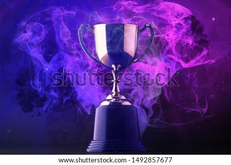 Trophy on smoke on dark blue futuristic background for e-sport winner concept.