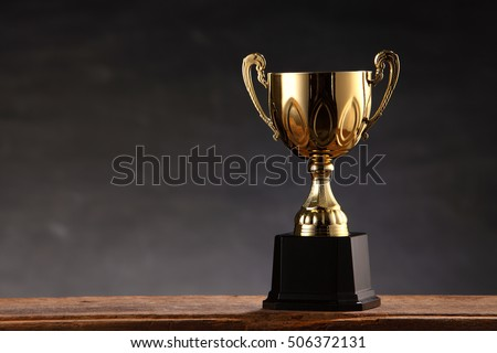 trophy on top of old wooden table in front of blackboard #506372131