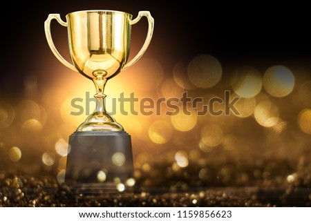 trophy over wooden table and dark background #1159856623