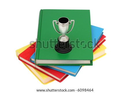 Trophy sitting on stack of books isolated on a white background