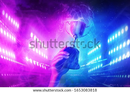 Trophy with smoke effect holding on hand and background blue and violet light for e-sport winner event.    Photo stock ©