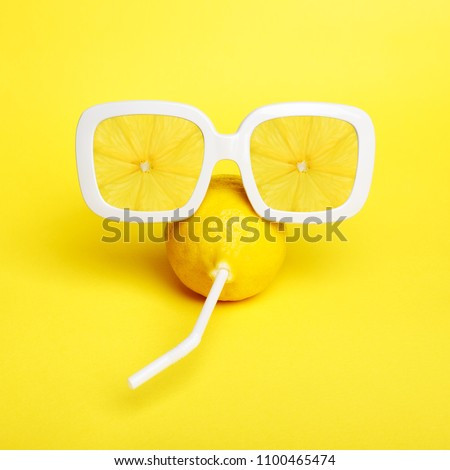 Tropic Lemon in vintage sunglasses with lemon slices reflection. Minimal fashion summer mood concept. Trendy monochrome yellow.