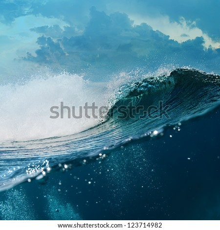 Tropical background design template. Cloudy Seaview Big Breaking surfing ocean wave in daylight with underwater part