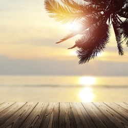 Tropical background with wooden empty table, coconut palm tree and beautiful beach at sunset