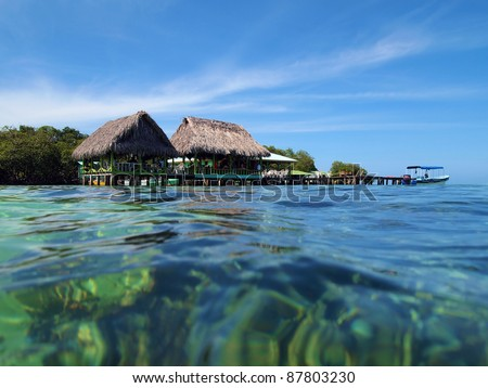 Tropical bar restaurant on stilts with thatched roof over the Caribbean sea, archipelago of Bocas del Toro, Panama