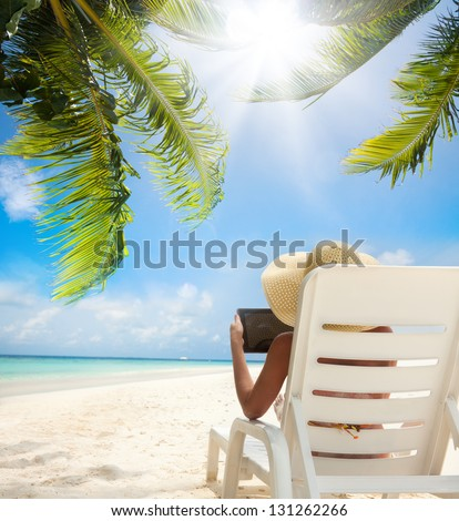 Tropical beach and woman relaxing with tablet computer sitting on the sun chair