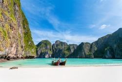 Tropical beach background. Panoramic views of Maya Bay with a longtail boat parked. overlooking white sand beach, clear water and beautiful sky. Phi Phi Leh island Krabi Province, Thailand.