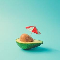 Tropical beach concept made of avocado fruit and sun umbrella. Creative minimal summer idea.
