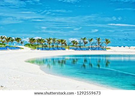 Tropical beach in Great Stirrup Cay, Bahamas. Sea shore, white sand, palm trees on blue sky. Summer vacation, recreation, resort. Paradise, peace, romance Travel traveling wanderlust