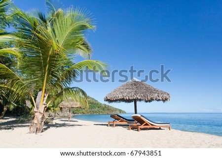 Tropical beach landscape with deckchair and parasol, from Nosy Be, Madagascar