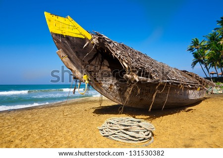 Tropical beach landscape with fishing boat at ocean coast under blue sky