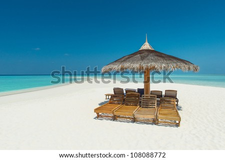 tropical beach on the maldives with canvas chairs and sunshades