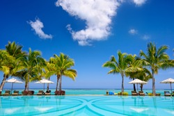 Tropical beach resort with  lounge chairs and umbrellas, Mauritius