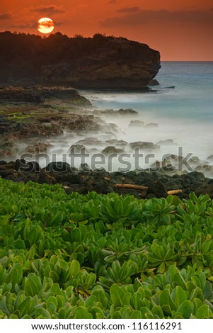 Tropical beach scene of waves crashing into rocks taken with a long exposure.