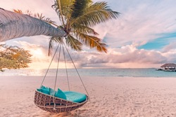 Tropical beach sunset landscape with beach swing or hammock and sunset sky white sand and calm sea for beach banner. Perfect beach scene vacation and summer holiday concept. Boost up color process