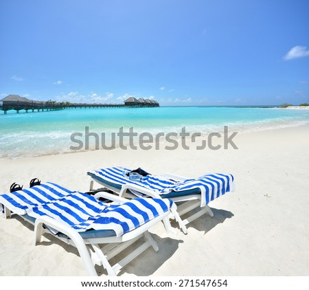Tropical beach vacation and travel concept -- Tanning beds and snorkeling equipment at the tropical beach