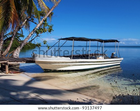 Tropical beach with a boat at dock, Caribbean sea