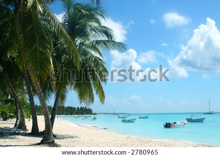tropical beach with boats in bay