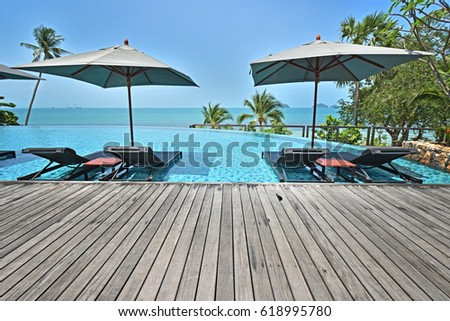Tropical beach with empty wooden platform and bright blue sky and swimming pool #618995780