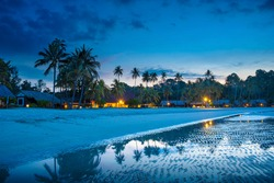 Tropical beach with palm trees and resort lights at night, low tide, on Bintan island, Indonesia