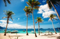 Tropical beach with palm trees, pilippine boats, blue sky, turquoise water and white sand. Paradise. Philippines, Palawan, El Nido. Wide angle, horizontal