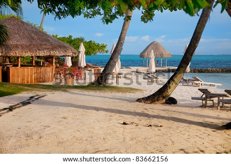 Tropical beach with restaurant and lounge beds