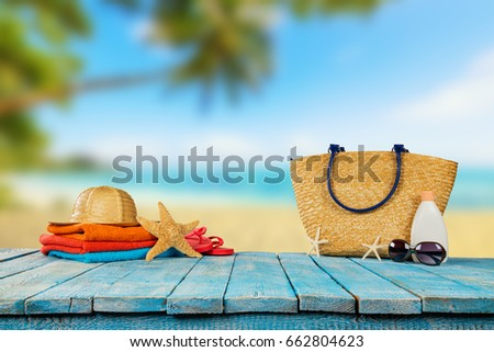 Tropical beach with sunbathing accessories placed on blue wooden planks, summer holiday background. Travel and beach vacation, free space for text. #662804623