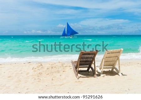 Tropical beach with two beach chairs facing the blue sea stock photo