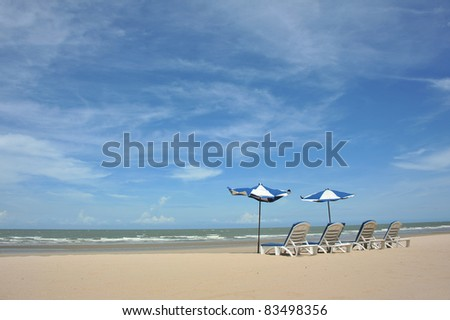tropical beach with umbrella and chairs