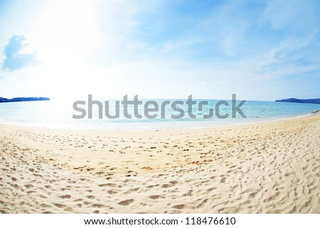 Tropical beach with white sand and calm sea with blue cloudy sky