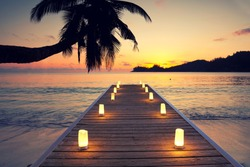 tropical beach with wooden jetty and candles, Indian Ocean at sunset. Holidays destination