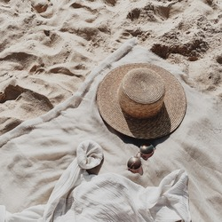 Tropical beautiful beach with white sand, foot steps, neutral blanket with straw hat, sunglasses and white shirt. Summer travel or vacation concept. Minimalistic background. Top view, flat lay