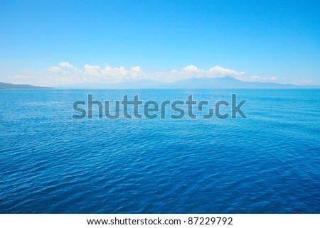 Tropical blue sea and blue sky with sun. Mountains on the horizon