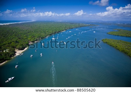 Tropical blue waterway with aerial view of luxury yachts and a city on the horizon