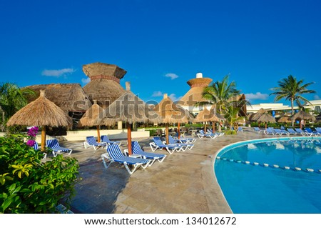 Tropical, caribbean swimming pool with some grass beach umbrellas in the luxury mexican resort. Bahia Principe, Riviera Maya.