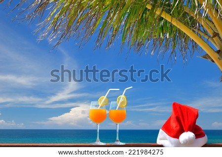 Tropical christmas vacations -- Two glasses of tropical fruit juice and red santa hat near the beautiful tropical sea with palm tree