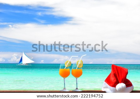 Tropical christmas vacations -- Two glasses of tropical fruit juice and red santa hat near the beautiful tropical sea