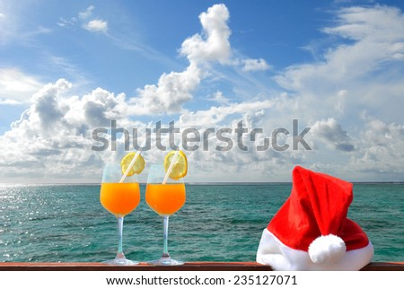 Tropical christmas vacations -- Two glasses of tropical fruit juice and red santa hat near the tropical green lagoon