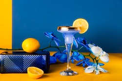 Tropical cocktail in glass with fresh lemon decor, blue orchid flower, glass texture podium on yellow and blue background. Trendy minimalism geometric drink composition. Contrast colors. Copy space