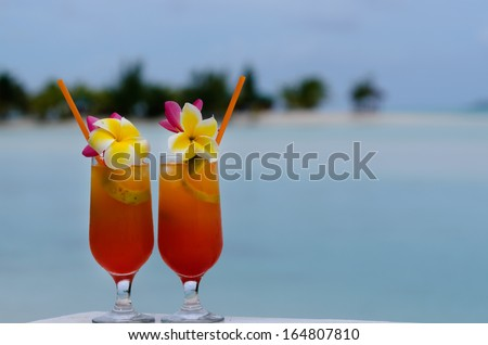 Tropical cocktails served outdoor on Pacific Island resort with turquoise water in the background. Concept photo of couples travel ,tourism, love, relationship, honeymoon.