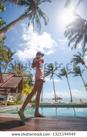 Tropical coconut summer landscape. Slim young woman on beautiful summer day. Summer vacation. People beauty fashion. Beauty portrait #1321594949