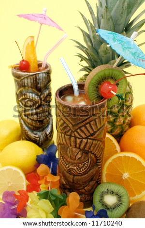 Tropical drinks served on tiki mugs and fruits display