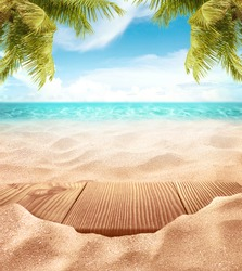 Tropical fine sandy beach with blured sea sun sky clouds background with wooden table top and empty space for product advertisement Montage of summer relaxation background
