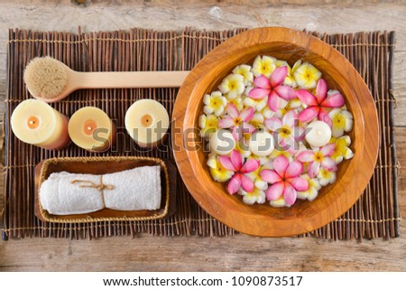 Tropical frangipani in a wooden bowl with candle, towel in basket on mat