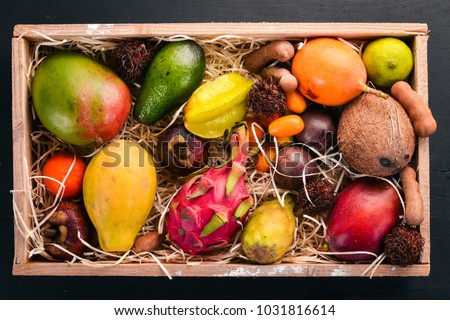 Tropical fruit in a wooden box. Papaya, Dragon Fruit, rambutan, tamarind, cactus fruit, avocado, granadilla, carambola, kumquat, mango, mangosteen, passionfruit, coconut.