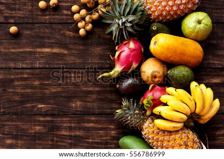 Tropical fruit on dark wooden background, top view #556786999