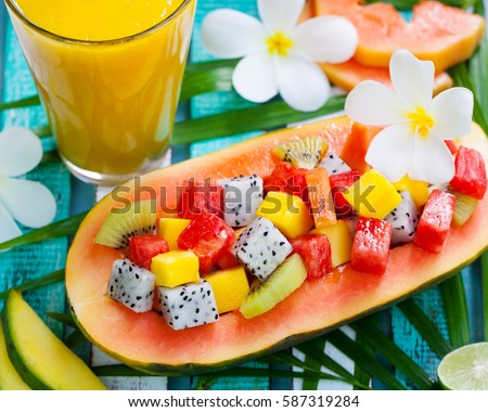 Tropical fruit salad in half of papaya with mango juice, smoothie on colorful wooden background with palm leaf and flowers. Top view #587319284