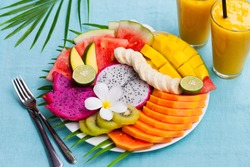 Tropical fruits assortment with mango smoothie, textile blue background.