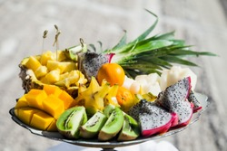 Tropical fruits laying on the dish served on the decorated table staying outdoor at sandy caribbean beach during destination wedding reception ceremony  and banquet.Beach catering for outdoors event